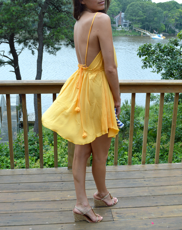 Yellow backless cocktail dress with striped clutch and nautical details