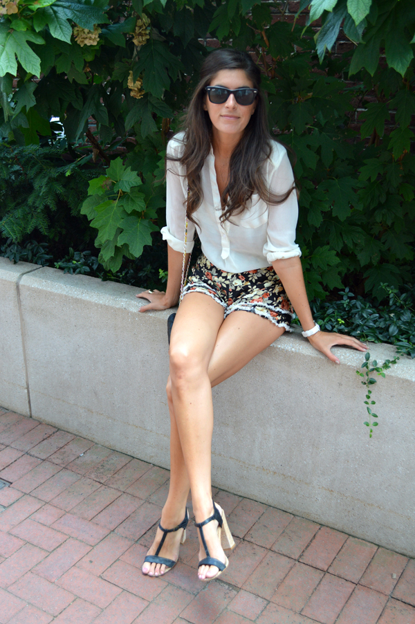Floral printed shorts with a sheer white blouse and strappy black heels