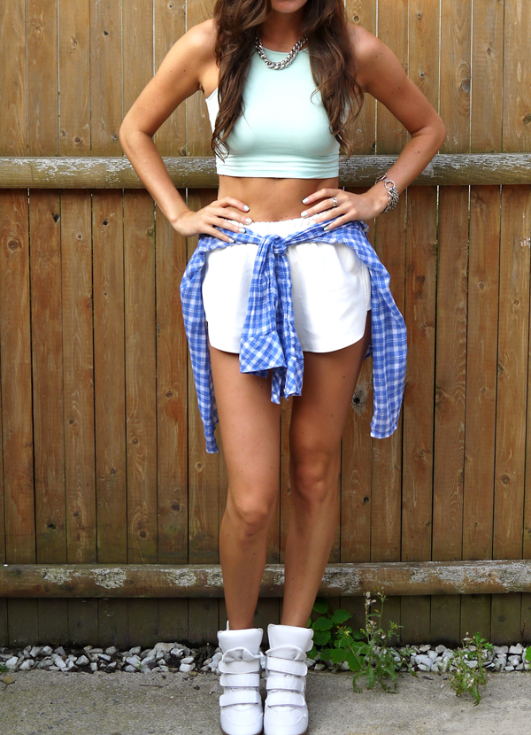 90's punk revival outfit: white leather shorts, crop top and shirt tied around the waist